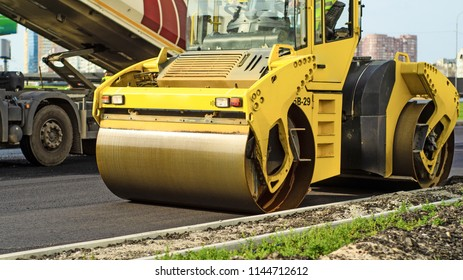 Yellow asphalt roller, road laying works during the day