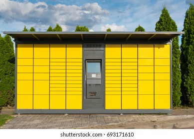 Yellow automated parcel terminal (parcel locker, post terminal) on the street in Poland, Europe.