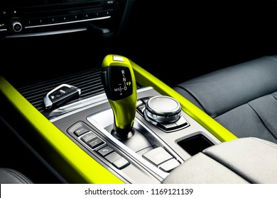 Yellow Automatic gear stick of a modern car. Maodern car interior details. Close up view. Car detailing. Automatic transmission lever shift. Black leather interior with stitching.