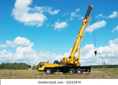 yellow automobile crane with rise n telescopic boom outdoors over blue sky