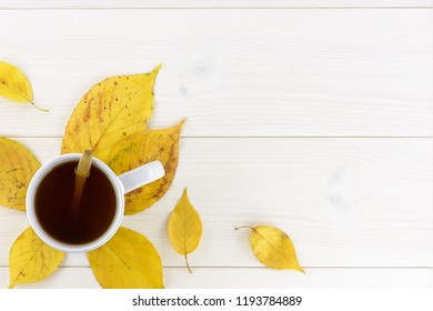 Yellow autumn leaves and a cup of hot tea on the white wood table