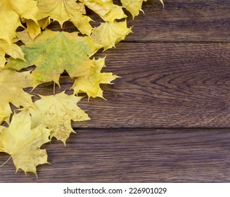 yellow autumn leaves lie wooden surface