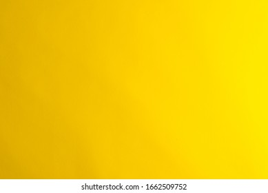 Yellow background made of real colored paper, illuminated by a soft light from the right.