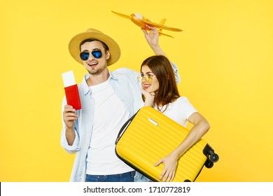 Yellow background man with a passport and a woman with a suitcase - Shutterstock ID 1710772819