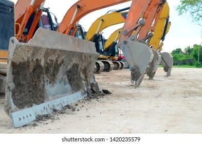 ฺOrange and Yellow backhoe bulldozer, grader including excavation equipment on the ground for construction site.