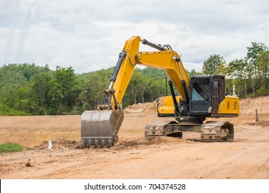 Yellow backhoe excavating soil and sand to construct water reservoir.