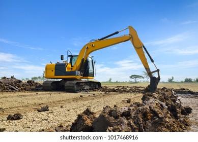 Yellow Backhoe working scoop soil in the field