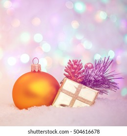 yellow ball and golden Gift box on snow. Defocused Christmas Bokeh