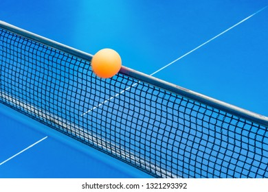 yellow ball hits the netting on a blue pingpong table