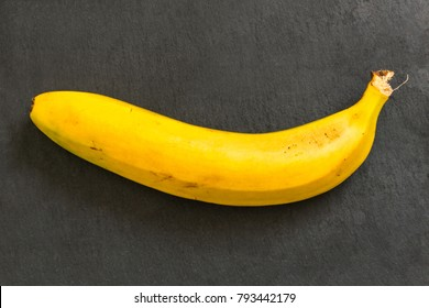 Yellow banana on black background. Side view