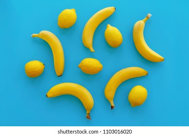 yellow bananas and lemons on bright blue paper, trendy flat lay. fruits modern image, top view. juicy summer vitamin abstract background. pop art style. minimalism pattern