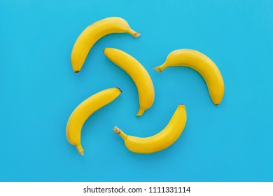 yellow bananas on bright blue paper, trendy background. fruits modern flat lay. juicy summer vitamin abstract background, top view. pop art style. banana pattern. blog