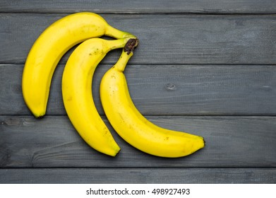 Yellow bananas on gray wooden surface