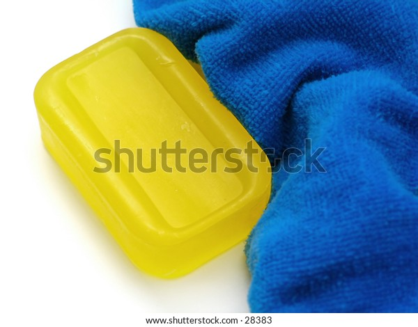 Yellow bar of semi-transparent soap next to a fluffy blue towel.