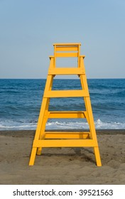Yellow baywatch chair in front of the sea