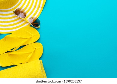 yellow beach accessories on turquoise blue background - sunglasses, towel. flip-flops and striped hat. summer is coming concept. holiday by the sea concept. flat lay of vacation accessories over blue