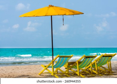 yellow beach chair on sand under shadow of beach umbrella  with blue sea background.