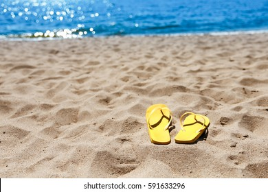 Yellow beach slippers on sandy beach, summer, bathing