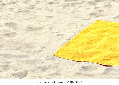 Yellow beach towel on sand