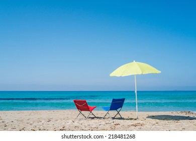 Yellow beach umbrella and two lounge chairs on a beach in Sardinia