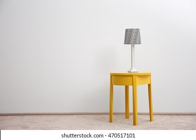 Yellow bedside table with lamp on white wall background
