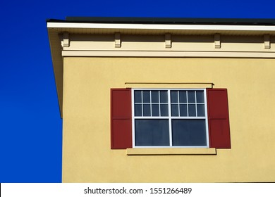 yellow beige wall window roof blue sky facade