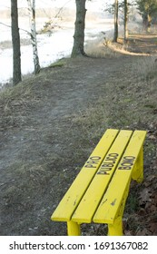 "Yellow bench on tourist path with Latin phrase ""pro publico bono"" painted on wooden boards. River Narew bank, resting place, nice view. Poland, Europe."