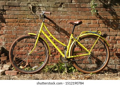 A yellow bicycle against a red brick wall