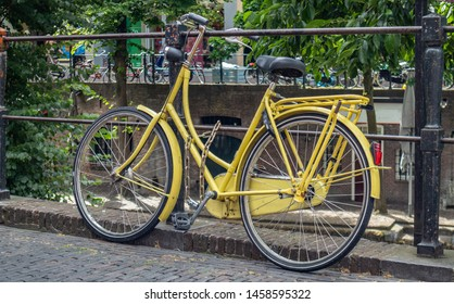Yellow bicycle. Bike yellow color locked on a river canal rail in Utrecht city historic center, Netherlands