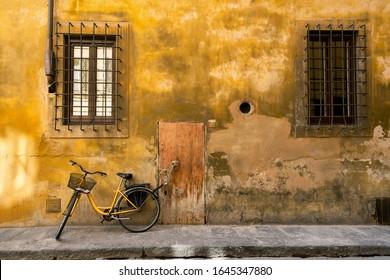 Vélo jaune attaché à une poignée de porte devant un joli vieux mur jaune et une porte en bois