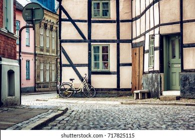 Yellow bicycle near the building facade with a window, Scandinavian style. Street in Lund, Sweden