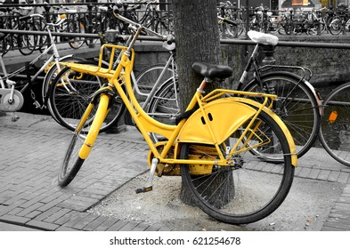 Yellow Bicycle Parked Up Near an Amsterdam Canal