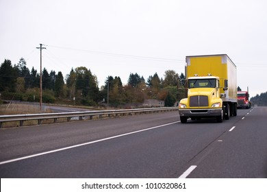 Yellow big rig semi truck with day cab for local delivery and box trailer for safety transporting goods moving in front of another truck on wide straight highway with trees on background