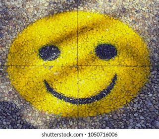 a yellow big smiley with laughing face on a paved walkway in closeup
