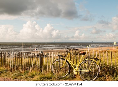 A yellow bike, fens on the dunes. Green ocean plants and kite surfers on windy and sunny day. Peaceful sunday rest and sport.