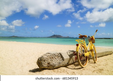 yellow bike leaning next to the concrete pole on the sandy beach