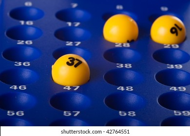 Yellow Bingo balls placed in the slots on a blue board
