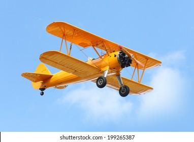 Yellow biplane on the blue sky.