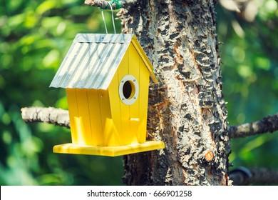 Yellow birdhouse next to a tree.