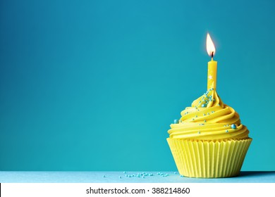 Yellow birthday cupcake on blue
