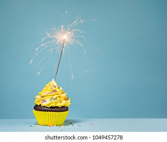 Yellow Birthday cupcake with sprinkles and a sparkler over a blue background.