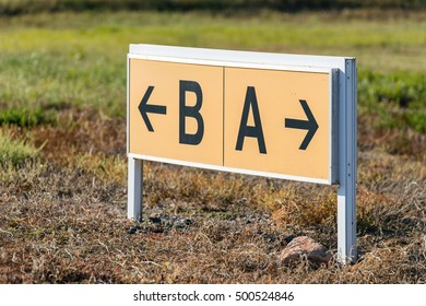 Yellow and black airport direction signs pointing taxiways.