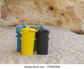 Yellow, black, blue, green colorful bins are installed for tourists and people on the ocean Portugal beach in order to throw waste, rubbish, garbage and sort it to protect environment and clean beach
