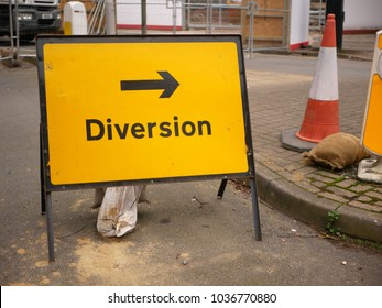 Yellow and black British diversion sign with arrow pointing right and traffic cone in urban environment