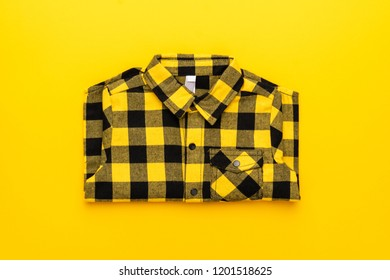 yellow and black checkered shirt on the yellow background. centre compositon