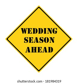 A yellow and black diamond shaped road sign with the words WEDDING SEASON AHEAD making a great concept.