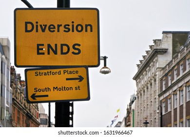 Yellow and black Diversion Ends sign with arrows pointing to Stratford Place and South Molton street, blurred building in background