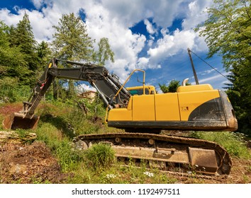 Yellow and black earth mover - crawler excavator, in a construction site in mountain