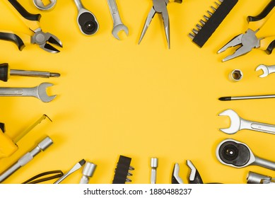 Yellow and black handy tools (pilers and screwdriver) isolated on yellow background