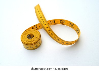 Yellow and black measuring tape on a white background, centimeters and inches, numbers fading away